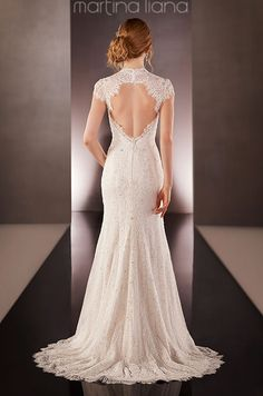 This sheath lace wedding dress features cap sleeves, sweep train, and a scalloped Lace keyhole back. Martina Liana, Spring 2015
