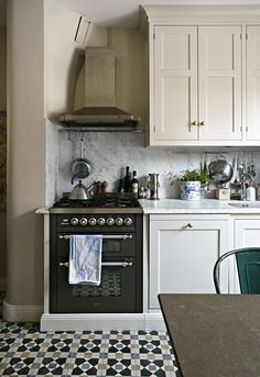 black stove, patterned tile floor, marble counter & backsplash