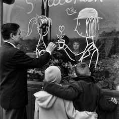 1958. C'est la Saint-Valentin. Raymond Peynet célèbre illustrateur, dessine un couple d'amoureux sur la vitrine d'un fleuriste. Photo : Jean Tesseyre / Paris Match