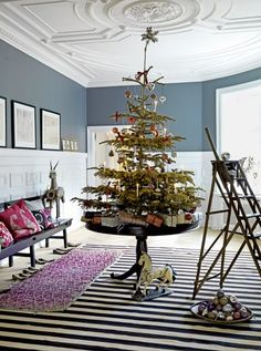 Untrimmed Christmas tree front and center within a white and grey room=my heaven