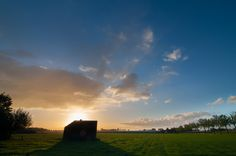See the sun rise over the dutch landscape. The WWII bunker is trying to fight the light, but will loose in a few moments.