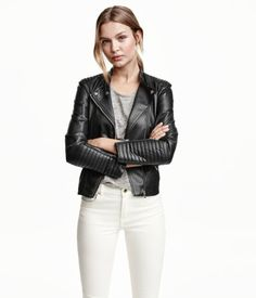 Black. Fitted biker jacket in soft imitation leather with quilted details. Small stand-up collar with tab and snap fastener, diagonal zip at front, pockets