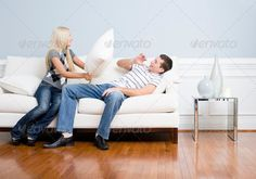Young Woman Smiling and Hitting Young Man With Pillow (beautiful, blond hair, blue wall, brown hair, caucasian, checkered top, copy space, couple, end table, female, flooring, full length, fun, glass, handsome, happiness, happy, hardwood, home, horizontal, house, indoors, inside, laminate, long hair, looking away from camera, male, man, people, pillow, pillow fight, playful, playing, portrait, Short Hair, smile, smiling, striped shirt, Studio Shot, twenties, two, vase, white, white sofa…