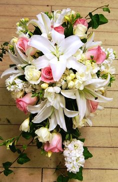 The big lillies in this could be replaced with more roses or ranunculus  and the greenery with a type of spray flower....  Cascade Bouquet by Georgianne Vinicombe at Monday Morning Flower and , via Flickr