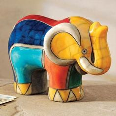 Artisans in South Africa use raku pottery techniques to create this colorful elephant. The bright color-block pattern is inspired by the beadwork and painted homes that are artistic hallmarks of the northeastern Ndzundza Ndebele people. Elephants symbolize steadfastness and wisdom--a pair of curved tusks even frames South Africa's coat of arms.