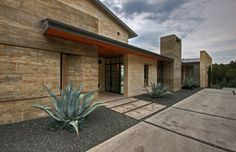 Rough hewn concrete forms with Jeruselum Gold (?) stone work.  Hill Country Residence - modern - exterior - austin - Cornerstone Architects