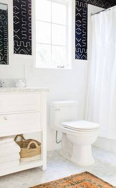 Black and white wallpaper in white bathroom