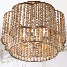 A distinctive scalloped frame encircles a cylindrical metal frame with multiple rows of round aged wood beads. Pair two of these singular chandeliers above a large dining room table or kitchen island. Chandeliers, Beaded Chandelier, Chandelier Shades, Chandelier Lighting, Lamp Shades, Dinning Room Light Fixture, Light Fixtures, Large Dining Room Table, Aging Wood