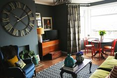 The Luxurious Little Home of Sooz Gordon. Dark green-grey wall paint and matching chevron rug. Natural floors. Black dining table with red chairs, green and blue velvet seating, black leggy coffee table.