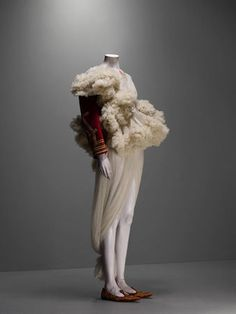 * Alexander McQueen (British, 1969–2010). Ensemble The Girl Who Lived in the Tree, autumn/winter 2008–9. Jacket of red silk velvet embroidered with gold bullion and trimmed with white shearling; dress of ivory silk tulle. Photo Sølve Sundsbø