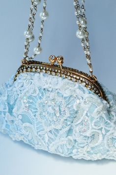 Exquisite heirloom handbag with a subtle blue hue that peeks through unique appliques and bridal lace on the front and back.