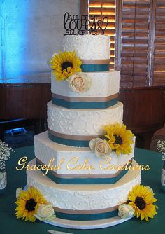 Elegant Hexagon and Round Ivory Butter Cream Wedding Cake with Taupe and Teal Ribbon accented with fresh Sun Flowers and White Roses