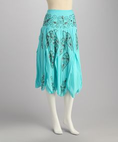Lightweight cotton and bright with a teal hue, this piece is a pretty pick. It's abloom with romance as seen in its floral embroidery and handkerchief hem.Measurements (size M): 31'' long100% cottonHand wash; hang dryImported