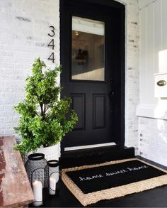 I like the simplistic look of the house address, the black door, the welcome mat (both) and the plant