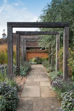 An oak pergola, weathered to an attractive silver gray, marks the entrance to the house, ushering visitors down a York stone pathway. Modern Garden Design, Landscape Design, Modern Design, Garden Stones, Garden Paths, Amazing Gardens, Beautiful Gardens, Big Leaf Plants, York Stone