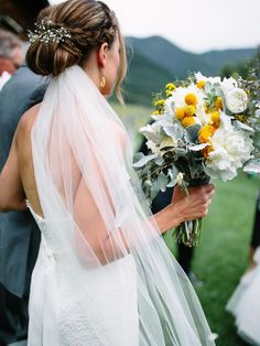 Tuck the veil under a chic, braided bun and accent with small flowers for an effortless-looking wedding day hairstyle.