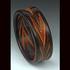 by Martha Collins. This Helical Mosaic bracelet has 12 different species of wood with artist-dyed veneers and is made of 1000 pieces with Ebony edges.