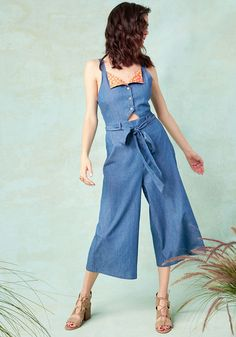 <p>Picturing yourself, in this chambray jumpsuit, cruising into the corner coffee shop is easy to do because it'll soon be you! With its clear buttons and waistline sash fastened neatly and its midriff cutout and wide, cropped legs looking coolly contemporary, this ModCloth namesake label romper is a smooth outfit move. Plus, its orange floral bodice lining 'n' back smocking are cute, comfy style bonuses!</p>