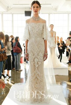 Brides.com: . Off-the-shoulder tulle wedding gown with flutter sleeves, softly flared skirt and silver threaded Chantilly lace underlay, embroidered all over with lace-like ivory thread work and organza ribbons, Marchesa