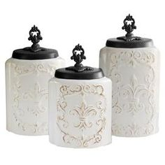 """Add classic appeal to your entryway console table or living room etagere with these earthenware canisters, showcasing a weathered fleur-de-lis motif and finial tops.  Product: Small, medium and large lidded canisterConstruction Material: EarthenwareColor: White and blackFeatures: Finial lids included  Dimensions: Small: 9.3"""" H Medium: 10.4"""" HLarge: 11.8"""" H"""