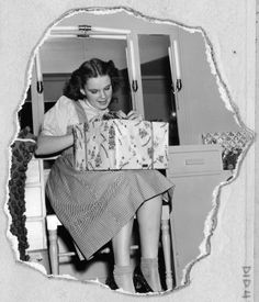 Judy Garland takes a break to open a present on the set of the film, whose complex production required the actors to show up at dawn six days a week.