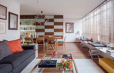 Na sala em L de 40 m², as ideias realizadas pelos arquitetos Domingos Pascali e Sarkis Semerdijan. Entre elas, um painel de luz indireta, que em parte foi aproveitado para expor as garrafas do morador