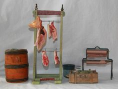German shop accessories for butcher and fishmonger, ca. 1920.   Meat wooden stand (29cm), fish barrel (12.5cm), Fish wooden box (10cm), Tragand meat parts with metal hooks and 2 fish, reel seat (12cm) with two paper rolls, functional spring mechanism.