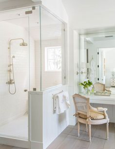 A pair of gilt mirrors add some shimmer to the all white master bathroom…