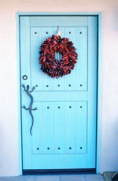 Our front door in Tucson...gecko door pull designed by local blacksmith, speakeasy window is under wreath with 'bars' made from saguaro cactus ribs