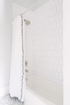 Classic white bathroom features floors clad in Bouquet IV Terrazzo tile from The Cement Shop that lead to a drop in bathtub accented with a shower surround of Cocoon mosaic tiles from Walker Zanger's 6th Avenue collection which can be concealed with a French tassel shower curtain from Serena and Lily.