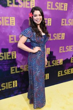 Auli'i Cravalho attends Elsie Fest at Central Park SummerStage in a floor length maxi dress in navy blue with red flowers