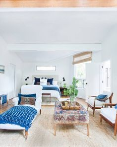 White, blue and grown-up Boho chic bedroom. More world-traveler than hippie. Huge ottoman upholstered with a gorgeous Moroccan rug, white upholstered chaise and chairs with vibrant blue textiles, clean white walls, bleached wood floors and lots of light.