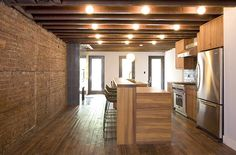 Exposed brick, exposed beams, salvage flooring with modern counters and appliances. Perfect combo.