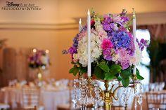 This colorful floral arrangement atop an elegant gold candelabra is a showstopper #Disney #wedding #reception #decor #centerpiece