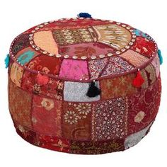 """Add a pop of color to your home library or living room seating group with this tribal-inspired pouf, crafted from cotton and showcasing tassel accents.  Product: PoufConstruction Material: CottonColor: MaroonFeatures: Made from recycled materialsDimensions: 12"""" H x 22"""" Diameter"""