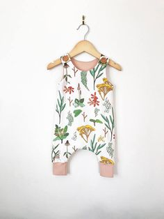 This button shoulder romper in floral print is perfect for your styling little lady ! Its perfect for fall and can easily be layered for cooler days. It pulls up easily and secures with two wood buttons at the shoulders. So cute and functional! We line the top and finish the cuffs with