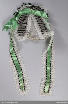 1860s cap of white lace (looks to be spotted net and blonde) trimmed with green silk satin ribbons and bows and black velvet ribbon. Upplandsmuseet, Sweden. Note strong similarity to 1865 Frank Leslie's Lady's Magazine cap illustration.