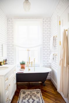 White subway tiles, chevron flooring and brass hardware in the bathroom