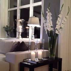simple tall glass tank vases with white candles and white gladioli