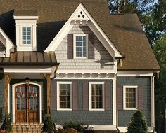 Cedar Shingles in Sand & Weathered Grey make the wood details shine on this home.