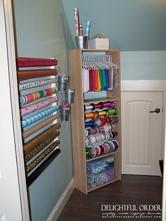 LOVE this idea! They used cheap curtain rods to hang the wrapping paper (as well as the tissue paper rod, etc.), and coat hangers to drape the tissue paper!