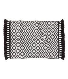 Black/white patterned. Reversible, jacquard-weave bath mat in cotton with fringe along short sides.