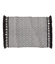 Black/White pattern. Reversible, jacquard-weave bath mat in cotton with fringes along the short sides.