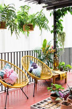 Varanda tem clima zen com piso de cimento queimado vermelho, poltronas Acapulco e plantas pendentes.