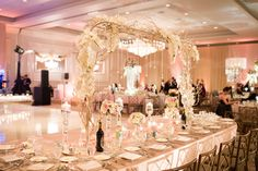 Wedding reception sweetheart table decor highlights the natural pastel flower bouquets and floating candles. Table also spotlights a unique arch with white flowers, gold tree branches and crystals hanging down.   Location: Drury Lane  Address: 100 Drury Lane, Oakbrook Terrace, Illinois 60181