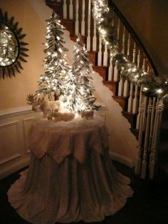 Snow scene created on a round decorator table, covered in a cloth that hangs on the floor and topped with a tree skirt. Love the flocked trees with the white lights.