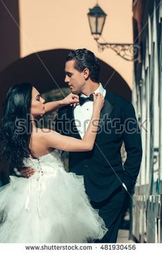 young wedding couple of sexy girl with brunette hair and pretty face in white bride dress and handsome man in black groom suit standing near street lamp of building arch sunny outdoor