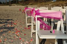 White padded garden chairs accented with your choice of chair sashes - adds a little elegance to any beach ceremony......  Created by Simple Elegant Weddings
