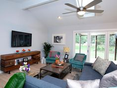 A skylight and 12-foot accordion bi-fold door let plenty of natural light in, while the doors also show off a view of the beautiful backyard from this airy living room. A contemporary blue sectional pairs nicely with the more rustic TV console, as well as the industrial-style coffee table.