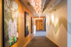 A wide gold chevron stripe visually leads residents through this eclectic hallway. It's a portrait gallery of sorts where the distinguished guests on display are some of Jackson Hole's (where the house is located) most notable occupants.